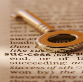 a key lying in open dictionary next to definition of success